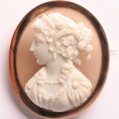 High relief hardstone cameo brooch of a woman in profile to the left, white on grey background.  The brooch can also be worn as a pendant by using the loop. Three dents on the frame.  42 x 49mm  €2200  www.Osprey.fr Gray Background, Vintage Jewelry, Profile, Paris, Jewels, Woman, Antiques, Pendant, Grey
