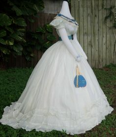 Another view of the muslin ballgown c.1865/6 shown with a bertha c.1865/6, belt with buckle c.1865 and mirrored fan c.1860s