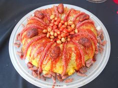 It's a Chamoy Fruit Cake-it's made up of jicama, cucumber and mango, topped with chamoy & tajin and accented with mango gummys and tamarindo gummy strips. The center is filled with Japanese Peanuts(cacahuates japoneses) and the base is surrounded by Tamarindo-wrapped green apple slices.