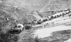 A pioneer wagon train winding down through Echo Canyon in 1868.
