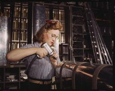 Operating a hand drill at North American Aviation, Inc, a woman is working in the control surface department assembling a section of the leading edge for the horizontal stabilizer of a plane,  [click on this image to find a documentary and analysis of the large scale entrance of American women into the paid labor force during World War II in order to fill positions abandoned by American men fighting abroad]  Photo credit: Alfred T. Palmer — in Inglewood, CA.