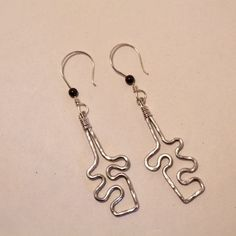 Judy Freyer Thompson's Jigsaw Puzzle Earrings, Contemporary Wire Jewelry. Forging, Forging Jewelry, Jewelry Forging, Texturing, Wire Wrapping, Wrapping, Wire Wrapping Jewelry. I have become somewhat addicted to aluminum wire lately. #wirejewelry