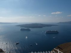 Cruise ships anchored in the caldera with Nea Kameni behind them