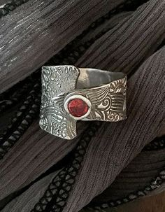 This fine silver (.999) ring has a interesting texture and is abloom with a passionate Hessonite Garnet gemstone. The ring overlaps on itself and envelops your finger and makes a wonderful adornment on your hand. Fine silver makes it elegant, the garnet and shape make it fun to wear with whatever you want-it will look good with everything.