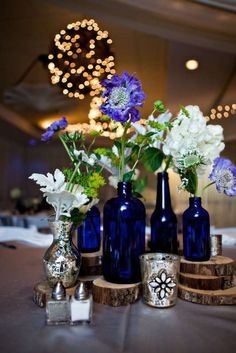 Cobalt blue bottles, silver mercury glass, and wood rounds with blue and white scabiosa, dusty miller, buplurem, and hydrangea to set the wedding centerpiece off perfectly. Rustic glam!