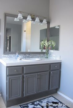 How to paint bathroom cabinets @ Home Idea Network---  love the gray color on the cabinets and the same color around the mirror.   Also love the shiny decal tile!