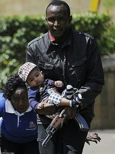 A security officer carrying a child and protecting a woman in the terrorist hostage situation