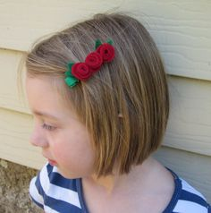 Three red felt roses on green ribbon covered hair clip on Etsy, $7.50 AUD