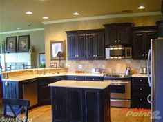 KITCHEN! black cabinets with corian countertops, tumble backsplash and stainless appliances - gorgeous!