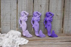 3 hand painted mermaid wall hooks. Shades of purple and lavender, lightly distressed and finished with a protective clear coat. Each hook has a hanger on the back. Perfect for your nautical or beach t