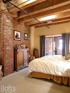 The master bedroom suite features exposed brick walls and Berber carpeting ...
