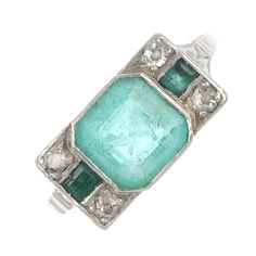 An Art Deco platinum emerald and diamond dress ring. The square-shape emerald, to the old-cut diamond and rectangular-shape emerald sides, floral engraved shoulders and plain band. Estimated total diamond weight 0.20ct. Weight 4.7gms.