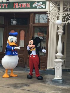 Donald and Mickey stand in front of the KITTY HAWK Bicycle Shop