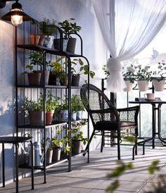 Liten balkong med grå hyllor fyllda med gröna växter, ett runt bord och en fåtölj i plastrotting