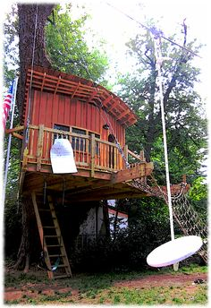 suspended single tree house with swing and flag pole