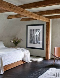 rustic bedroom in renovated farm house, neutral decor features wood beamed ceilings, black & white large scale art