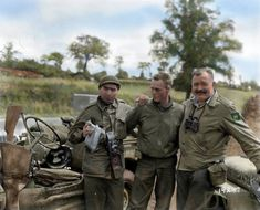 Robert Capa (the famous War Photographer), their driver - Pfc. Olin L. Tompkins and Ernest Hemingway (War Correspondent, novelist and journalist) standing by their 2nd Armored Division jeeps in Pont Brocard, Normandy on 30 July 1944.