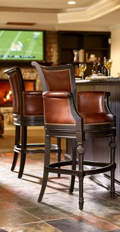 Chesterfield offers rare Neoclassic styling in a fully upholstered barstool. Its regal bearing is achieved through a curved crest rail and arms, English-inspired turned legs, and deep red oxblood leather.
