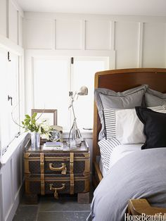 In the master bedroom of a Napa Valley ranch house designed by Ken Fulk, vintage Louis Vuitton suitcases are propped on wooden blocks to serve as a night table.   - HouseBeautiful.com