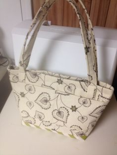 This purse is great for fall with heart shaped flowers. It has a chevron green bottom. Zipper closure. Inside has pockets for carrying cellphone, lipstick etc. available today @8706799126(4SALE)