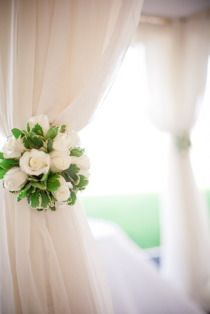 Wedding decors. White curtains with white roses and green leaves. Pretty. :)