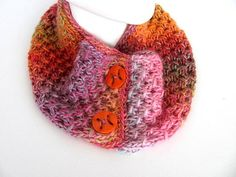 "This shaded yarn worked up beautifully into a unique cowl. Pinks, purples, & oranges slip from one to the other in this knitted piece. Two vintage orange buttons embellish the front.The piece measures 28"" around #zibbet"