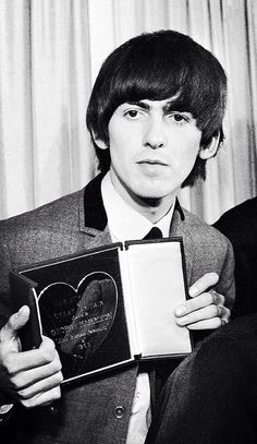George showing his award he received with the Beatles from the Variety Club of Great Britain as best act of 1963. March 1964