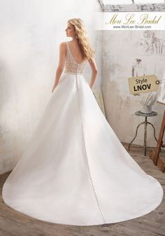 Dress Style LNOV  Understated and Elegant, This Stunning Marcella Satin A-Line Bridal Gown Features a Crystal Beaded Sheer Back and Waistline. Covered Buttons Trim the Back and Train. Available in White/Silver, Ivory/Silver. Shown in Ivory/Silver. Inventario de Bogotá Talla 6 Color Ivory