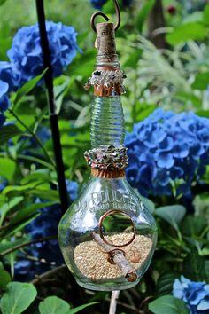 Artistic recycled glass bottle bird feeder.