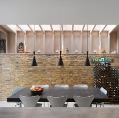 Tom Dixon tall beat lights in modern London kitchen with brick wall and eat-in kitchen i like the idea of exposed brick work for the kitchen. Tom Dixon, Oak Bookshelves, Bookcase Door, Brick Wall Kitchen, Grande Table A Manger, House Worth, Wooden Staircases, Tower House, Brick Wallpaper