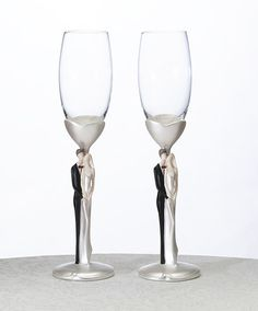 """Standing 10"""" tall, this pair of glasses is unique for the design of its stem. The glass is held by a resin stem and base. Accenting the stem is a painted resin bride and groom in loving embrace. Also available in African-American."""
