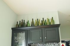 Wine bottles above the kitchen cabinets.  I kind of adore this idea...why didn't I think of it before?