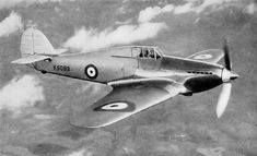 """Hawker Hurricane K5083 in flight, with test pilot P.W.S. """"George"""" Bulman in the cockpit. Right front quarter view, from slightly above."""