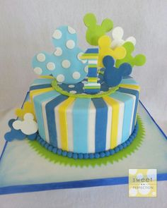 Mickey Mouse cake for a 1st birthday.  Blue, baby blue, green and yellow. Stripes and spots. Mickey silhouette cut outs.  Not my design although I'm not sure who the original cake artist is.