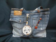This denim tote bag (recycled) is a unique model and is composed of: * on the front: 2 pockets (those of jeans), 5 buttons of different colors and sizes are sewn on one of the pockets + 2 dog buttons sewn at the base of the handles, multicolored sequins are stuck on the other pocket, a