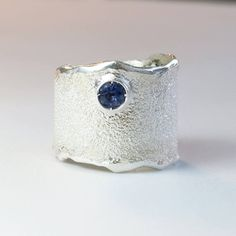 B Blue iolite ring, blue stone ring, silver ring, blue gem ring, silver solitaire ring, wide silver ring, greek jewelry, greek ring blue iolite wide silver ring, Blue iolite Solitaire Ring, blue gem ring, Rough textured wide silver ring foster texture , contemporary ring made in Greece