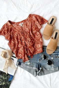 Summer outfit flatlay featuring a ruffle top, nude slides, handkerchief, shorts, and sunnies.