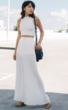 Wide leg white accordion pleated pants with a short underlining and side zipper closure. Made of light breathable fabric for a comfortable style.