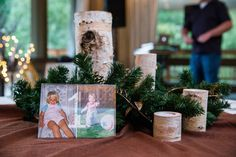 Wood and pine cone tablescape with table numbers made from couple's baby pictures.