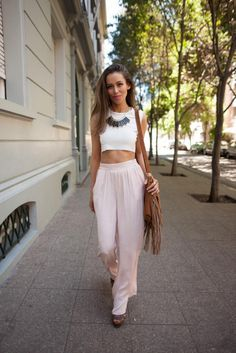 White crop top, statement black necklace and pale pink loose trousers
