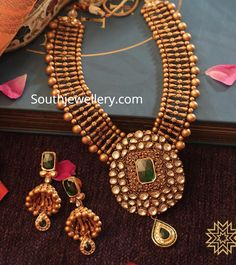 22 carat gold antique necklace with polki and emerald pendant paired with matching jhumkas by Manubhai Jewellers. 22 carat gold antique necklace with polki and emerald pendant paired with matching jhumkas by Manubhai Jewellers. Antique Jewellery Designs, Gold Earrings Designs, Gold Jewellery Design, Necklace Designs, Fancy Earrings, Gold Jewelry Simple, Manubhai Jewellers, Emerald Pendant, Antique Necklace