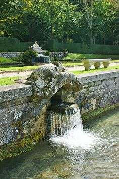 Carved stone heads with water flowing at Chateau de Courances