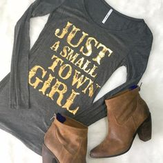 Just A Small Town Girl LS Tee We know we're not JUST small town girls - but why not enjoy your roots in this adorable top? Slim fit, lightweight material, great to toss in for a chilly morning or evening in the summer, perfect under a vest when the days are getting frosty! Note: top is charcoal, not black as shown on model. ChicBirdie Tops Tees - Long Sleeve