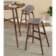 The Axel bar stools by Simple Living features a mid century modern style with rubberwood legs and upholstered seats. The seats come in grey linen or black faux leather. These stools are ideal for your contemporary bar, kitchen or dining area.