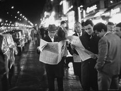 frenchmen reading newspaper reports of j.f.k.'s assassination
