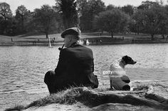 A man and his dog relax at the edge of a pond on Hampstead Heath, London. Original Publication: Picture Post - 5987 - Hampstead Heath - unpub.