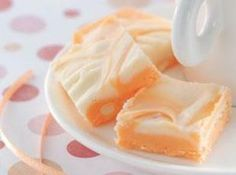 Marbled Orange Fudge Recipe 2-1/2 cups sugar   2/3 cup evaporated milk   1/2 cup butter, cubed   1 package (10 to 12 ounces) white baking chips   1 jar (7 ounces) marshmallow creme   3 teaspoons orange extract   12 drops yellow food coloring   9 drops red food coloring