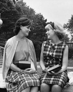 Schoolgirls having a conversation holding books, 1950s.