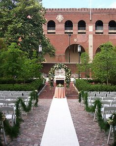 transform stoner courtyard into a wedding venue with a center isle and decorated seating