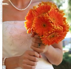 Susanne carried a bouquet she'd arranged herself with her favorite flower, orange gerbera daisies, tied with an ivory ribbon.